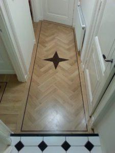 klassieke visgraat vloer met ornament in een hal geplaatst